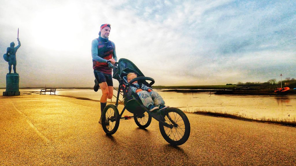 Man running outdoors with child in Nipper Sport pushchair