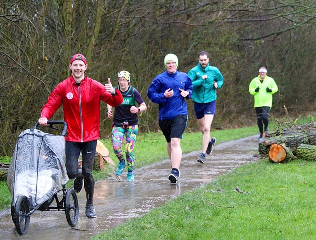 Man running in the rain with child in Nipper Sport pushchair