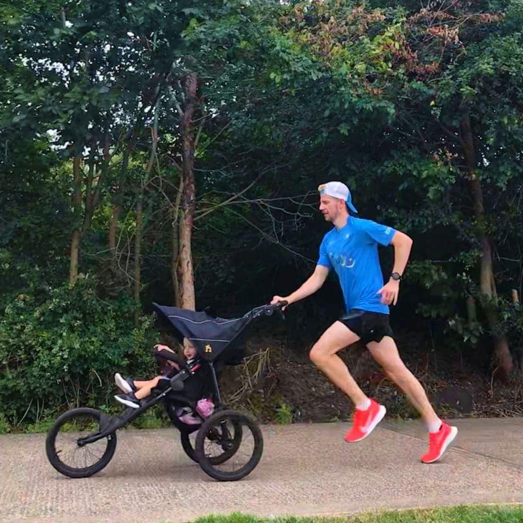 Man running with child in Nipper Sport pushchair